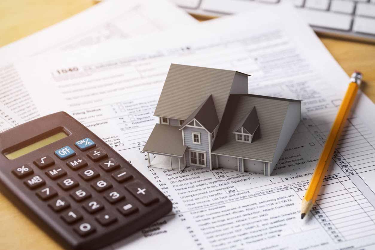 家の模型と電卓と鉛筆